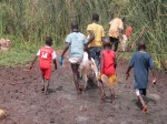 Boys trekking through the mud