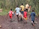 Boys trekking through the mud
